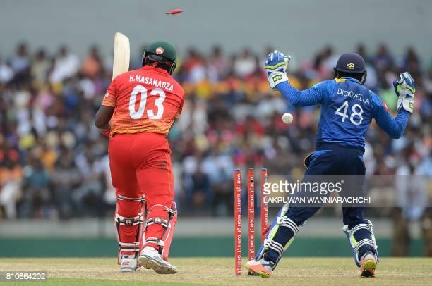 Zimbabwe's cricketer Hamilton Masakadza gets dismissed by Sri Lankan spinner Wanindu Hasaranga as wicketkeeper Niroshan Dikwella looks on during the...
