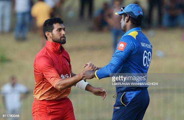 Zimbabwe's cricketer Sikandar Raza is congratulated by Sri Lankan cricket captain Angelo Mathews after their victory in the fifth oneday...