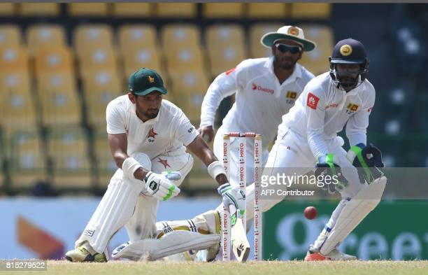 Zimbabwe's cricketer Sikandar Raza plays a shot as Sri Lankan wicketkeeper Niroshan Dickwella and cricketer Dimuth Karunaratne look on during the...