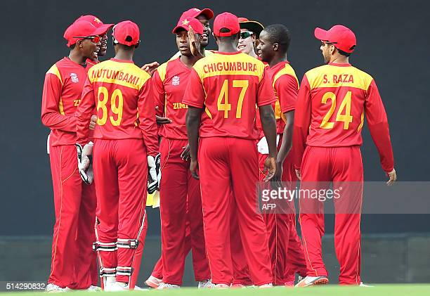 Zimbabwe's Donald Tiripano celebrates with teammates after taking the wicket of unseen Hong Kong batsman Ryan Campbell during the opening match of...