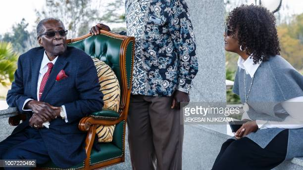 TOPSHOT Zimbabwe's former President Robert Mugabe speaks with his wife Grace Mugabe during a press conference held at his Blue Roof residence in...