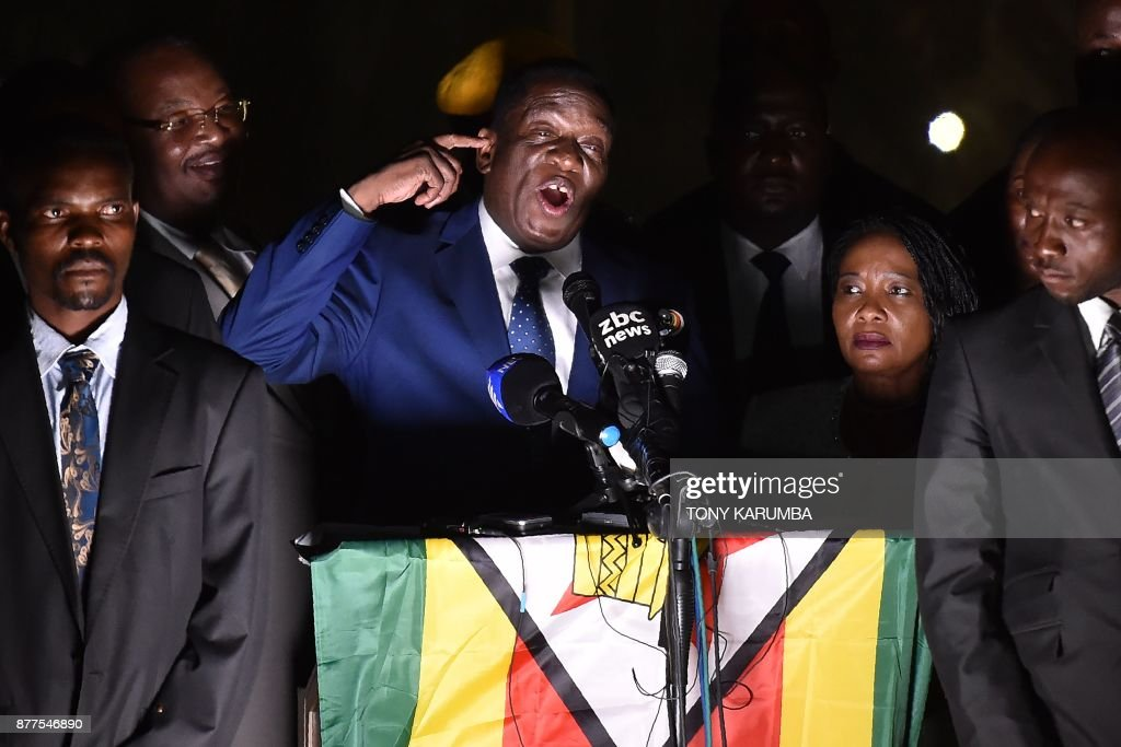 TOPSHOT - Zimbabwe's incoming president Emmerson Mnangagwa (3rd L) speaks to supporters flanked by his wife Auxilia (2nd R) surrounded by their bodyguards at Zimbabwe's ruling Zanu-PF party headquarters in Harare on November 22, 2017. Zimbabwe's former vice president Emmerson Mnangagwa flew home on November 22 to take power after the resignation of Robert Mugabe put an end to 37 years of authoritarian rule. Mnangagwa will be sworn in as president at an inauguration ceremony on November 24, officials said. KARUMBA