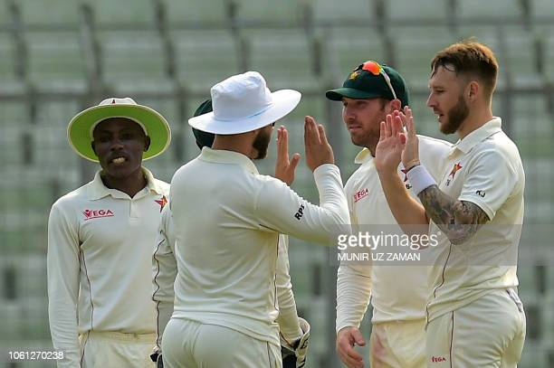 Zimbabwe's Kyle Jarvis celebrates with teamamtes after the dismissal of the Bangladesh's Liton Das during the fourth day of the second Test cricket...