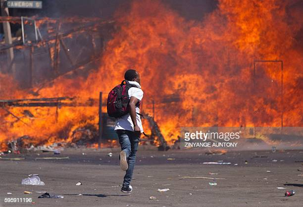 TOPSHOT Zimbabwe's opposition supporters set up a burning barricade as they clash with police during a protest for electoral reforms on August 26...