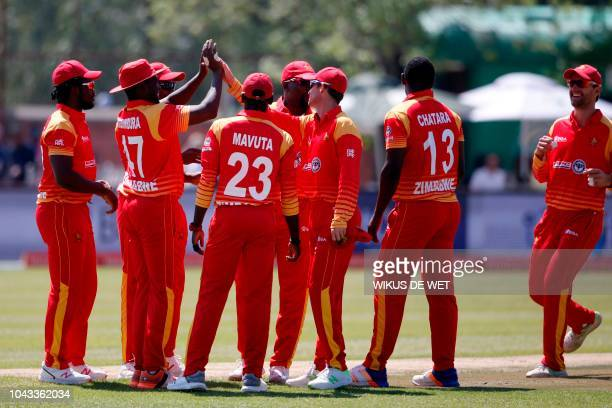 Zimbabwe's players celebrate after fielder Elton Chigumbura and bowler Tendai Chatara dismissed South Africa's Aiden Markram during the first One Day...