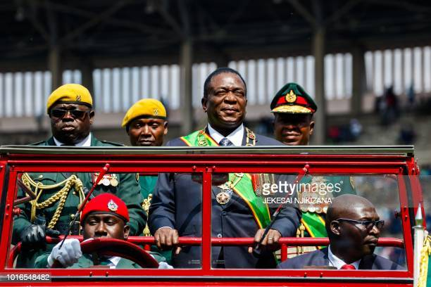 Zimbabwe's President Emmerson Mnangagwa inspects the guard of honour from a car during the Defence Forces Day celebrations held at the National...