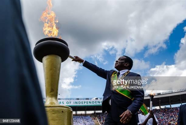 TOPSHOT Zimbabwe's President Emmerson Mnangagwa lights the Eternal Flame of Freedom during Zimbabwe Independence Day celebrations at the National...