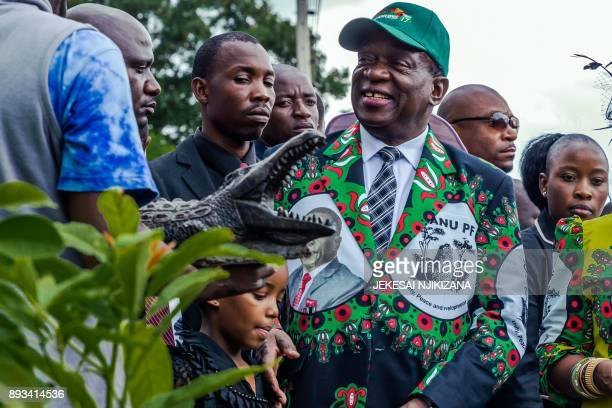TOPSHOT Zimbabwe's President Emmerson Mnangagwa receives a statue of a crocodile 'Ngwena' after planting a tree during the extraordinary conference...
