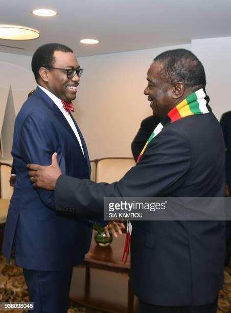 Zimbabwe's President Emmerson Mnangagwa shakes hands with African Development Bank's president Akinwumi Adesina on the sideline of the opening...