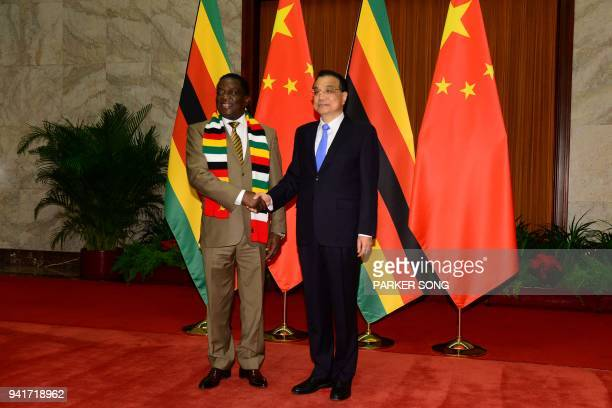 Zimbabwe's President Emmerson Mnangagwa shakes hands with Chinese Premier Li Keqiang before their meeting at the Great Hall of the People in Beijing...