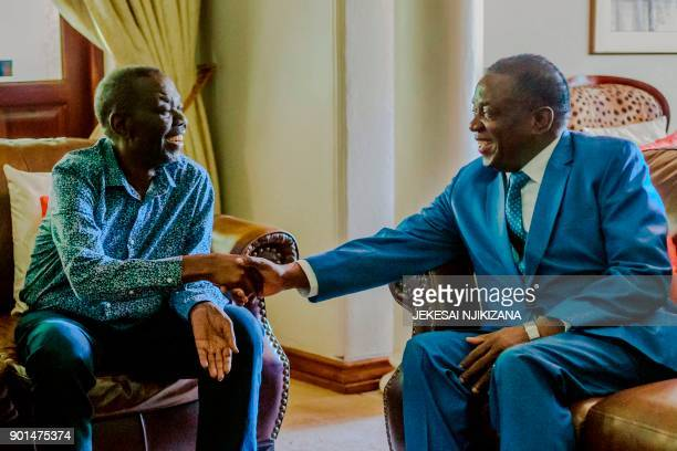 Zimbabwe's President Emmerson Mnangagwa shakes hands with the leader of the Movement for Democratic Change the country's main opposition party Morgan...