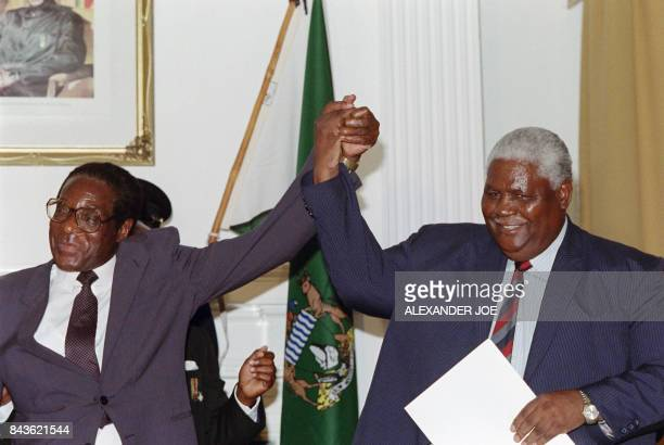 Zimbabwe's President Robert Mugabe and former President of Zimbabwe African People's Union Joshua Nkomo raise their fists 22 December 1987 in Nairobi...