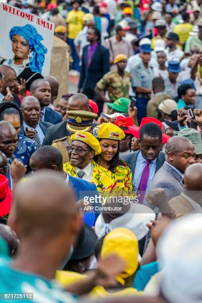 Zimbabwe's President Robert Mugabe and his wife Grace Mugabe arrive to greet party members and supporters gathered at his party headquarters to show...