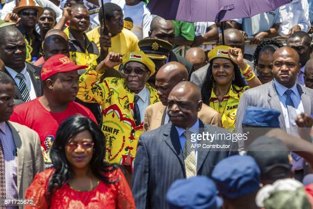 Zimbabwe's President Robert Mugabe and his wife Grace Mugabe raise their fists to greet party members and supporters gathered at his party...