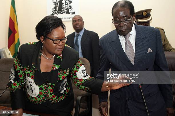 Zimbabwe's President Robert Mugabe and VicePresident Joice Mujuru are seen at a meeting of the ruling ZANUPF party headquarters on October 24 2014 in...