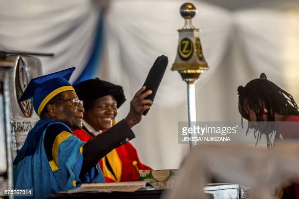 Zimbabwe's President Robert Mugabe caps a graduate during a graduation ceremony at the Zimbabwe Open University in Harare where he presides as the...