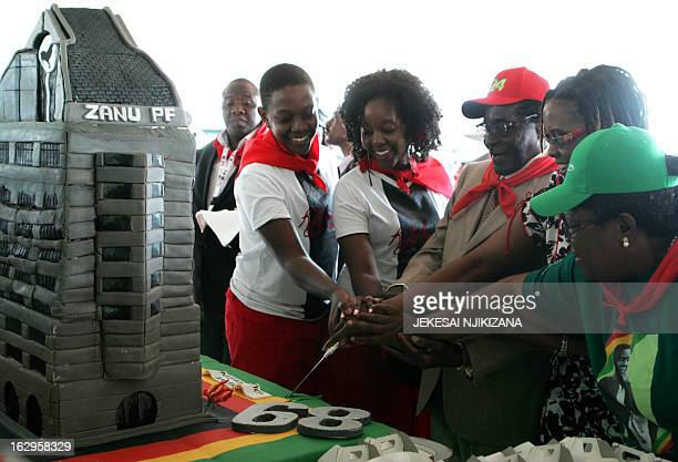 Zimbabwe's President Robert Mugabe cuts his birthday cake with the first family his children Chatunga Mugabe and Bona Mugabe and his wife Grace...