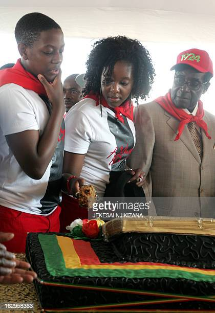Zimbabwe's President Robert Mugabe cuts his birthday cake with the first family his children Chatunga Mugabe and Bona Mugabe during a y21st February...