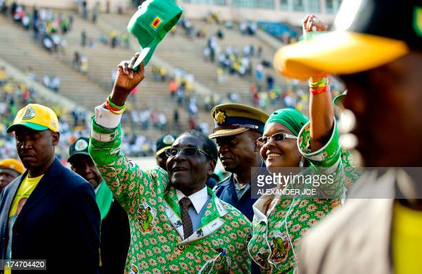 Zimbabwe's President Robert Mugabe greets his supporters alongside his wife Grace after his address at a rally in Harare on July 28 2013 Zimbabweans...