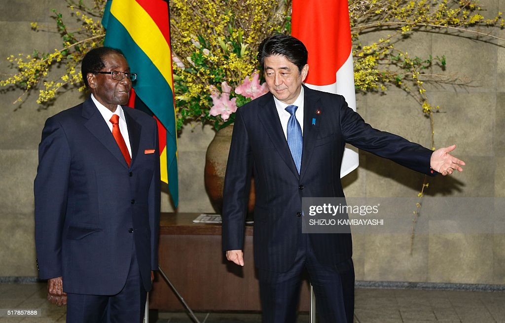 Zimbabwe's President Robert Mugabe (L) is greeted by Japan's Prime Minister Shinzo Abe prior to a meeting at Abe's official residence in Tokyo on March 28, 2016. / AFP / POOL / Shizuo Kambayashi