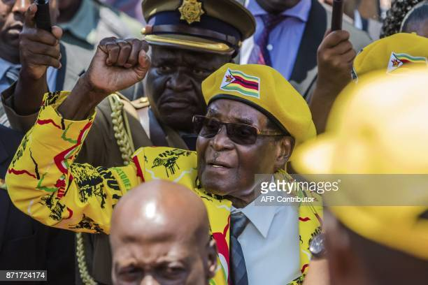 Zimbabwe's President Robert Mugabe raises his fist as he greets party members and supporters gathered at his party headquarters to show support to...