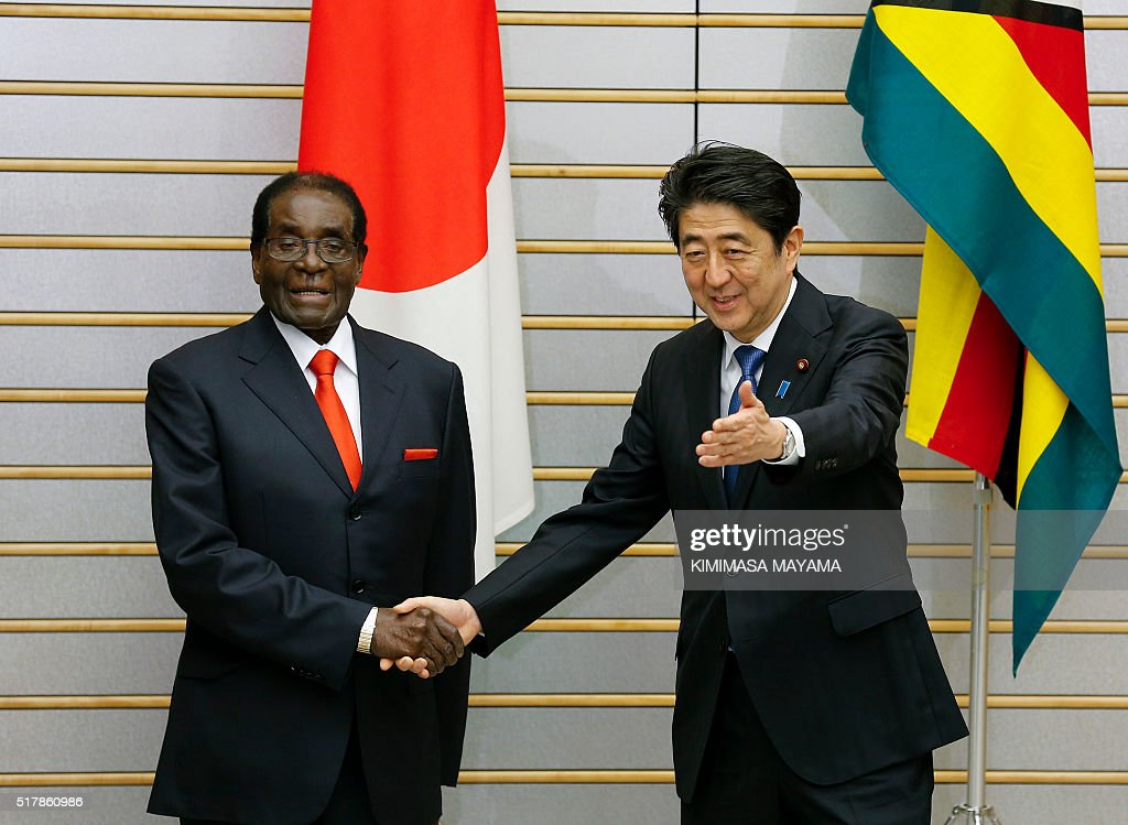 Zimbabwe's President Robert Mugabe (L) shakes hands with Japan's Prime Minister Shinzo Abe at the start of their talks at the latter's official residence in Tokyo on March 28, 2016. Mugabe arrived in Japan on March 27 for a five-day official working visit. / AFP / POOL / Kimimasa Mayama