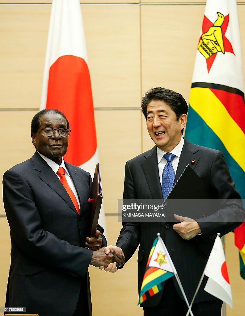 Zimbabwe's President Robert Mugabe (L) shakes hands with Japan's Prime Minister Shinzo Abe following a signing ceremony at the latter's official residence in Tokyo on March 28, 2016. Mugabe arrived in Japan on March 27 for a five-day official working visit. / AFP / POOL / Kimimasa Mayama