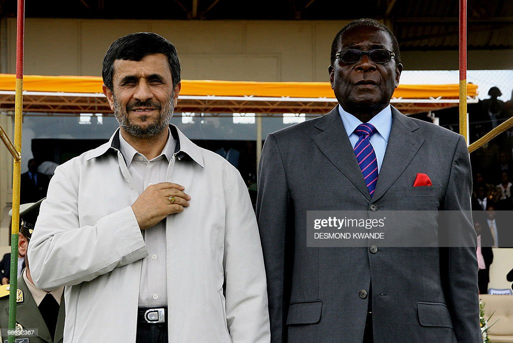 Zimbabwe's President Robert Mugabe (R) stands with Iranian President Mahmoud Ahmadinejad at a parade during the official opening of a trade fair on April 23, 2010 in Bulawayo. Iran's President Mahmoud Ahmadinejad on Friday accused world powers of trying to destroy the economies of Zimbabwe and his own nation, which faces the threat of toughened sanctions. AFP PHOTO/Desmond Kwande