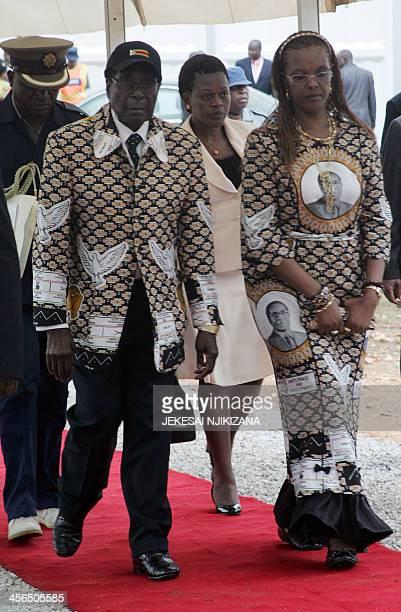 Zimbabwe's president Robert Mugabe walks his wife Grace Mugabe during the opening day of Zimbabwe's ruling ZanuPF party annual conference in Chinhoyi...