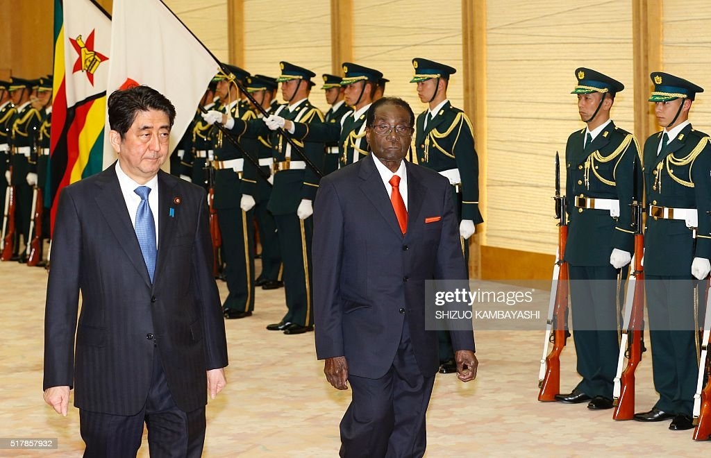 Zimbabwe's President Robert Mugabe (C) walks with Japan's Prime Minister Shinzo Abe (L) as they review a guard of honour prior to their meeting at Abe's official residence in Tokyo on March 28, 2016. / AFP / POOL / Shizuo Kambayashi