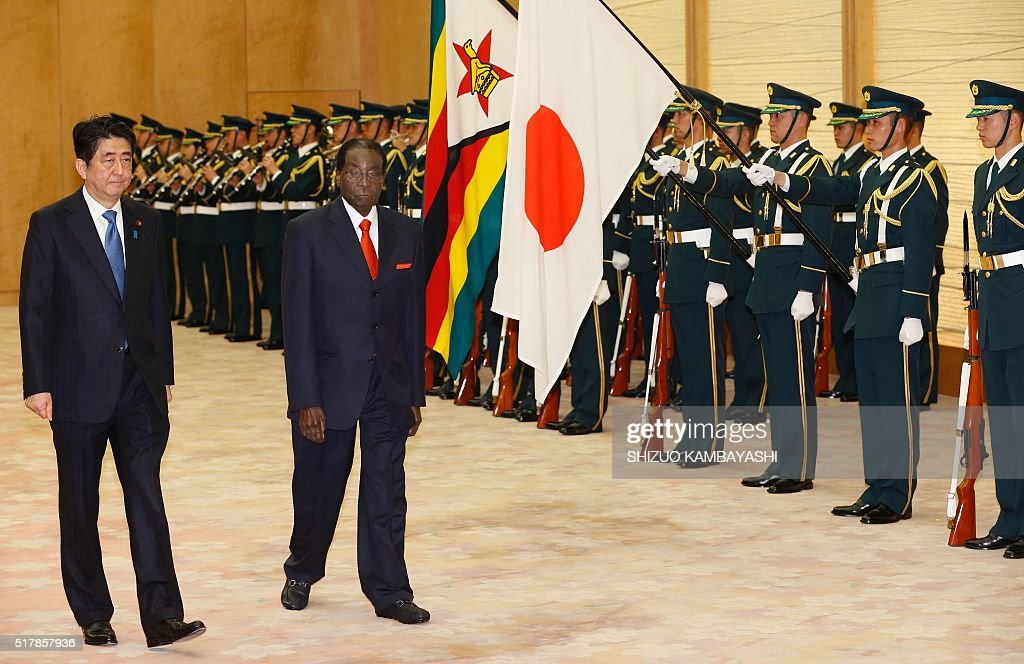 Zimbabwe's President Robert Mugabe (2nd L) walks with Japan's Prime Minister Shinzo Abe (L) as they review a guard of honour prior to their meeting at Abe's official residence in Tokyo on March 28, 2016. / AFP / POOL / Shizuo Kambayashi