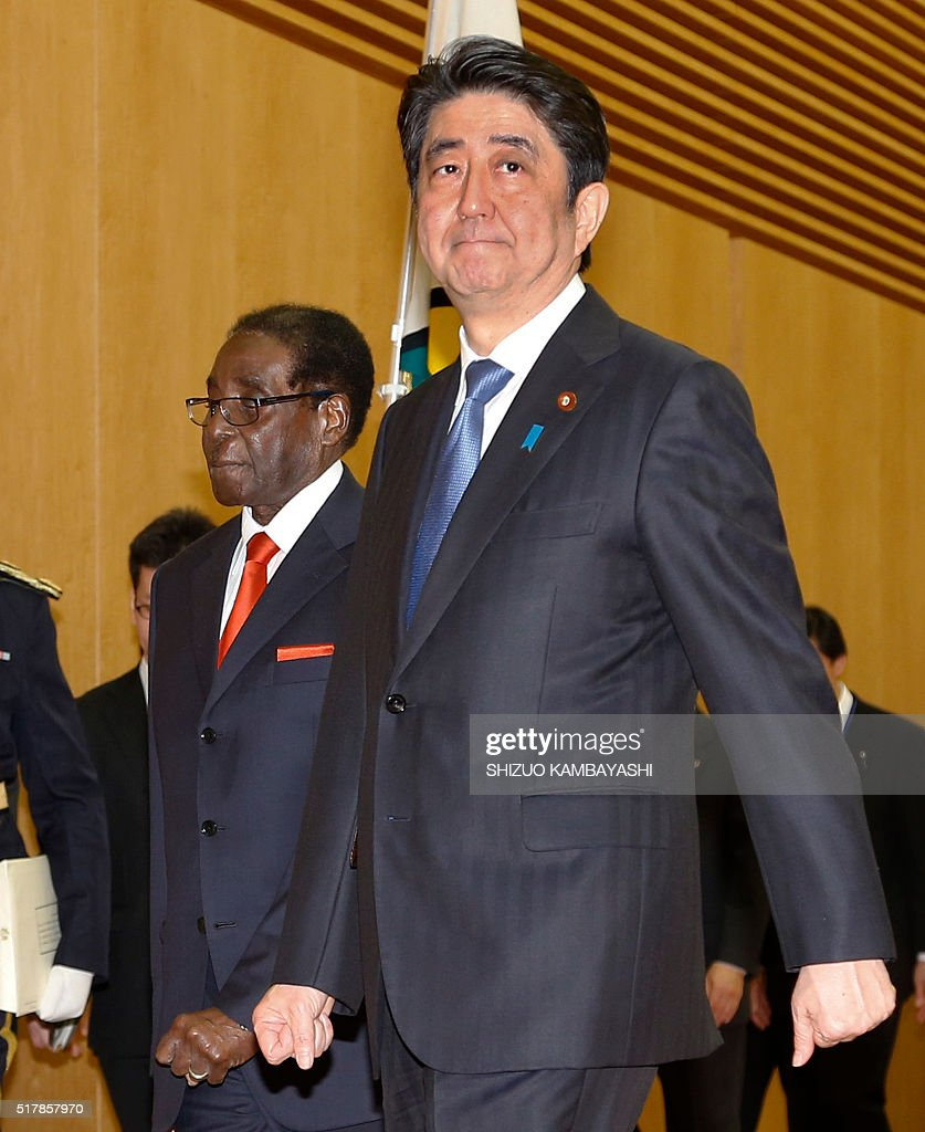 Zimbabwe's President Robert Mugabe (L) walks with Japan's Prime Minister Shinzo Abe (R) after being welcomed upon his arrival prior to their meeting at Abe's official residence in Tokyo on March 28, 2016. / AFP / POOL / Shizuo Kambayashi