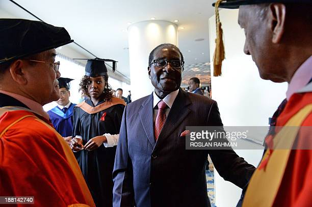 Zimbabwes President Robert Mugabe with his 24yearold firstborn child and only daughter Bona Mugabe attend the convocation at MDISUniversity of Wales...