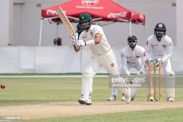 Zimbabwe's Sikandar Raza watches the ball after playing a shot as Sri Lanka's Niroshan Dickwella looks on during the first day of the second Test...
