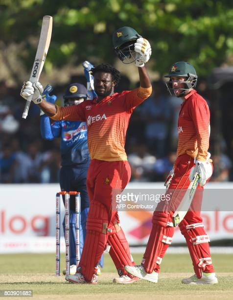 Zimbabwe's Solomon Mire celebrates after scoring his century as teammates Sean Williams look on during the first oneday international cricket match...