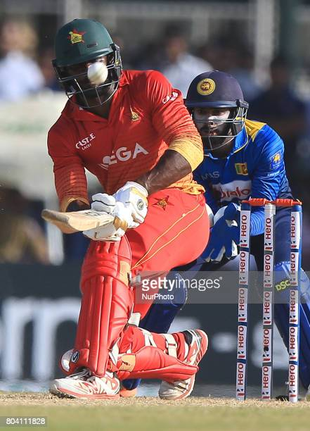 Zimbabwe's Solomon Mire plays a shot as Sri Lanka's Niorshan Dickwella looks on during the 1st ODI cricket match at the Galle International cricket...