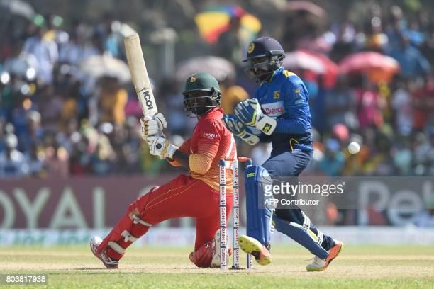 Zimbabwe's Solomon Mire plays a shot next to Sri Lanka's wicketkeeper Niroshan Dickwella during the first oneday international cricket match between...