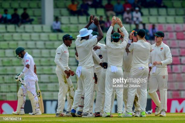 Zimbabwe's team celebrates the dismissal of the Bangladesh's Liton Das during the fourth day of the first Test cricket match between Bangladesh and...