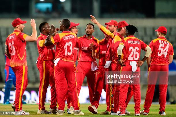 Zimbabwe's Tendai Chatara celebrates with his teammates after the dismissal of Afghanistan's Hazratullah Zazai during the second match between...
