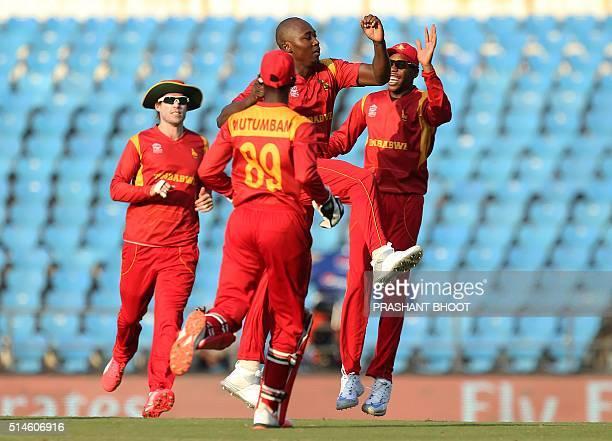 Zimbabwe's Tendai Chatara celebrates with teammates after the dismissal of unseen Scotland batsman Matt Cross during the World T20 cricket tournament...