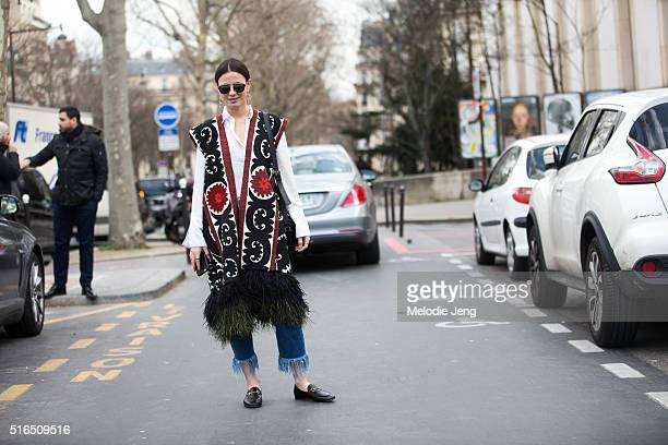 Zina Charkoplia wears Sandra Mansour feather gilet outfit with fringe jeans and Gucci loafers shoes at the Ellery show at Palais de Tokyo on March 07...