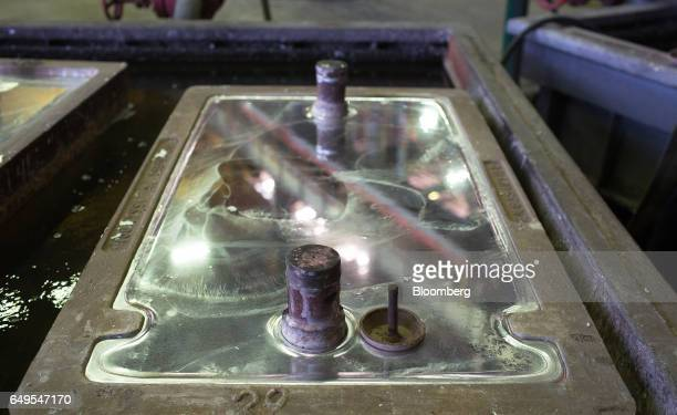 A zinc ingot cools in its mold in the rotary foundry room at the Chelyabinsk Zinc Plant operated by Ural Mining and Metallurgical Co in Chelyabinsk...