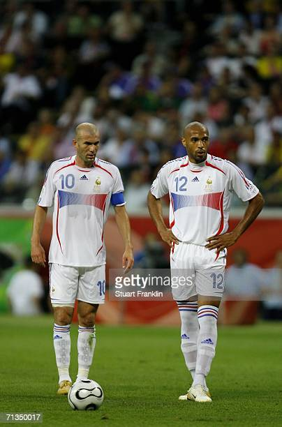 Zinedine Zidane and Thierry Henry of France stand over the ball as they wait to take a free kick during the FIFA World Cup Germany 2006 Quarterfinal...
