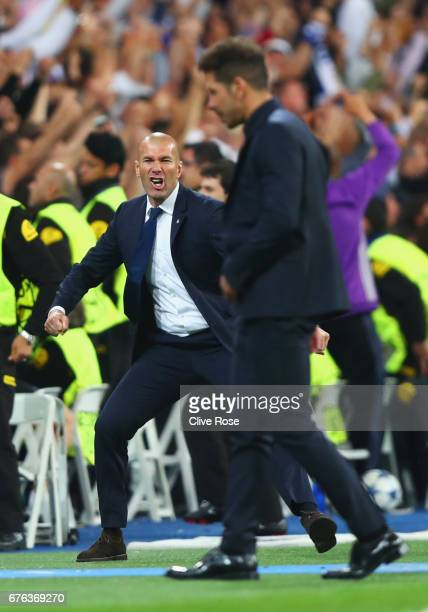 Zinedine Zidane head coach of Real Madrid celebrates as Cristiano Ronaldo of Real Madrid scores their second goal as Diego Simeone manager of...