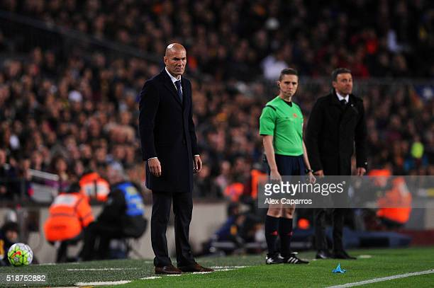 Zinedine Zidane Head Coach of Real Madrid CF looks on next to Luis Enrique Head Coach of FC Barcelona during the La Liga match between FC Barcelona...