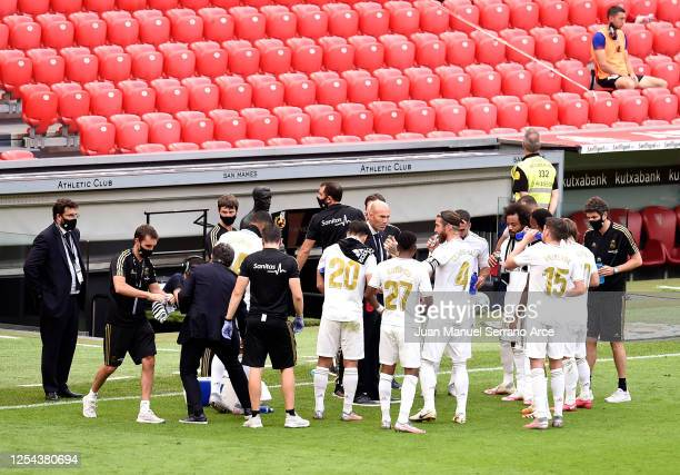 Zinedine Zidane Head Coach of Real Madrid speaks with his players during a scheduled rehydration break during the La Liga match between Athletic Club...