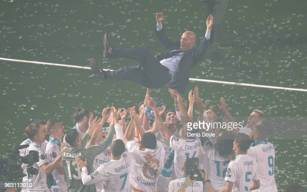 Zinedine Zidane, Manager of Real Madrid is thrown in the air by his players during celebrations at the Santiago Bernabeu stadium following their...