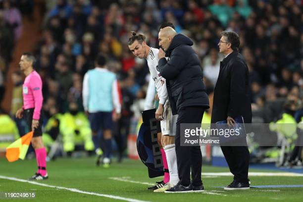 Zinedine Zidane, Manager of Real Madrid speaks to Gareth Bale of Real Madrid as he prepares to be substituted on during the UEFA Champions League...