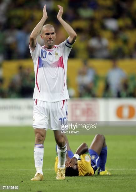 Zinedine Zidane of France applauds the fans following his team's 10 victory whilst a dejected Ze Roberto of Brazil lies on the pitch after the FIFA...