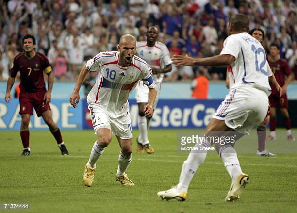 Zinedine Zidane of France turns away to celebrate with teammate Thierry Henry after scoring the opening goal from the penalty spot during the FIFA...